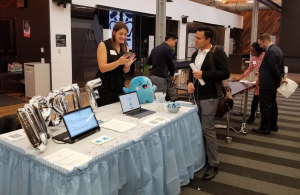 Woman showcasing project to male attendee